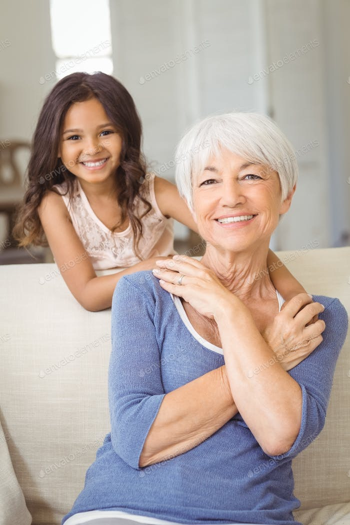 Portrait of smiling granddaughter embracing her grandmother in living room