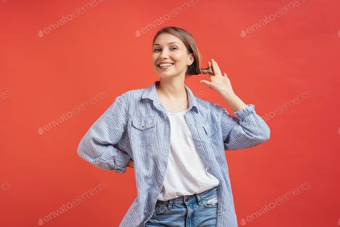 Attraktive junge Frau spielt mit ihren Haaren und lächelnd, während sie vor rotem Hintergrund stehen