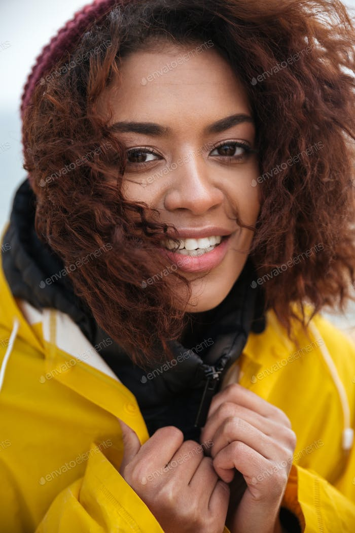 Smiling african curly young woman wearing yellow coat