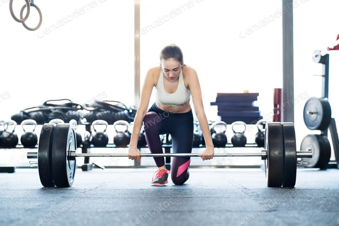 Beautiful young fit woman in gym lifting heavy barbell