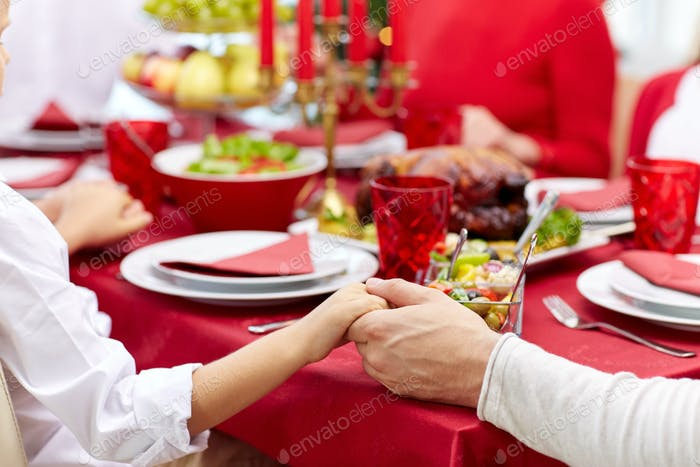 family having holiday dinner and praying at home