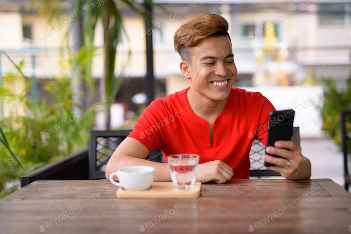 Happy young Asian man using phone at the coffee shop outdoors