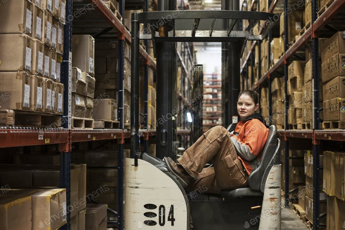 Caucasian female warehouse worker sitting in a motorized stock picker surrounded by products stored