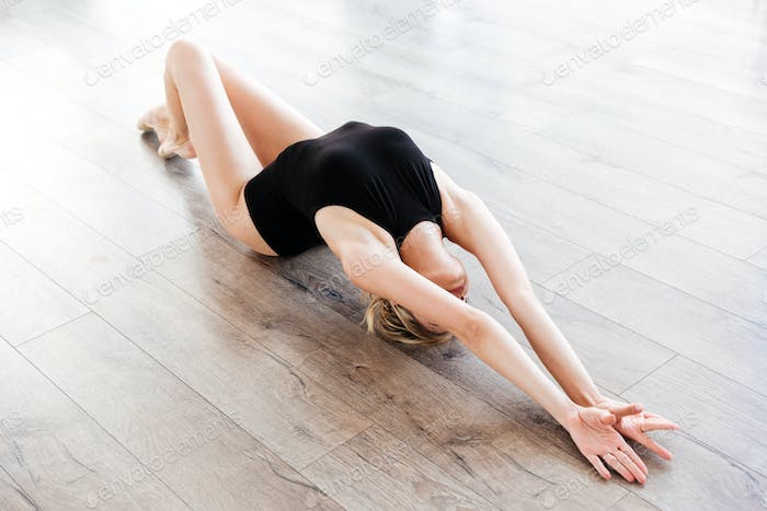 Sensual young woman ballerina lying and stretching on the floor