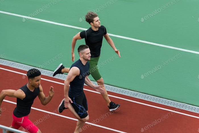 Handsome multiethnic athlete group run on running track