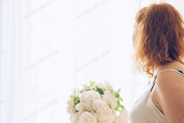 Young beautiful pregnant woman sitting near window at home
