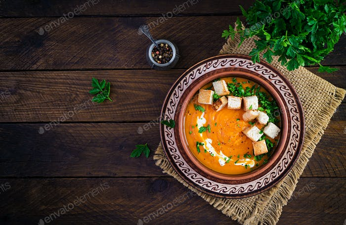 Kürbissuppe in einer Schüssel serviert mit Croutons und Petersilie.