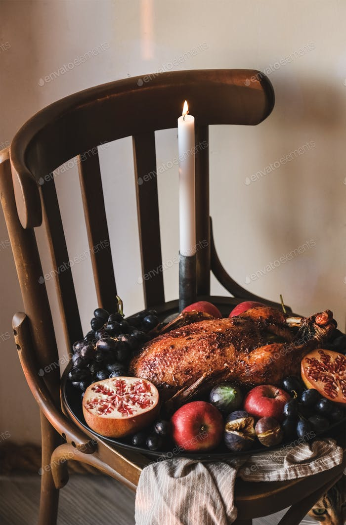 Whole oven roasted duck in fruits on wooden stool