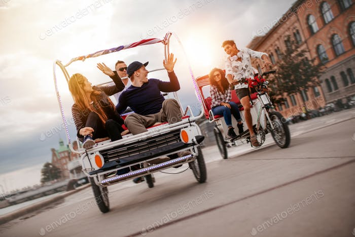 Group of friends having fun with two tricycles on road