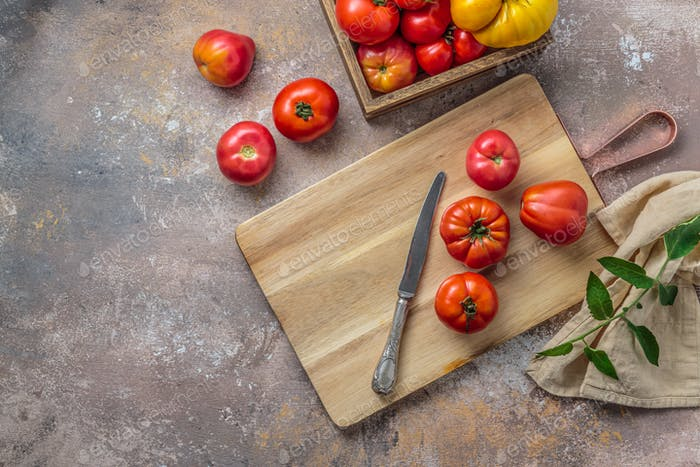 Cutting board with red tomatoes and knife, top view copy space