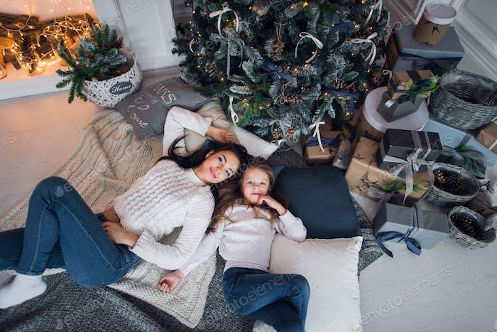 Schöne glückliche Familie Mutter und Tochter mit Geschenken rund um den Weihnachtsbaum sind auf dem Boden