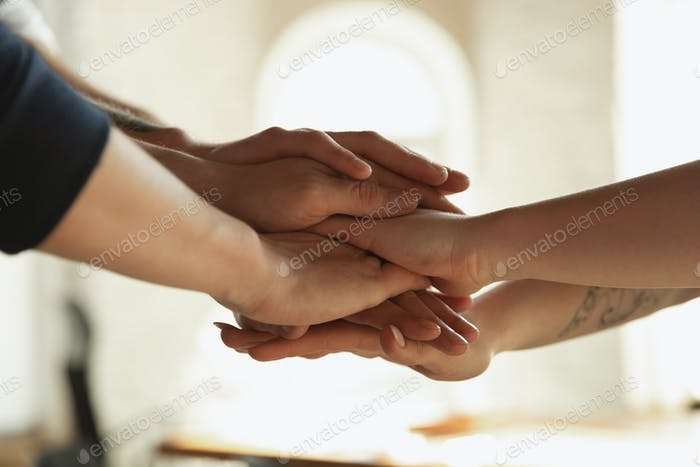 Close up of caucasian male and female hands, covering one another, team, friendship, business