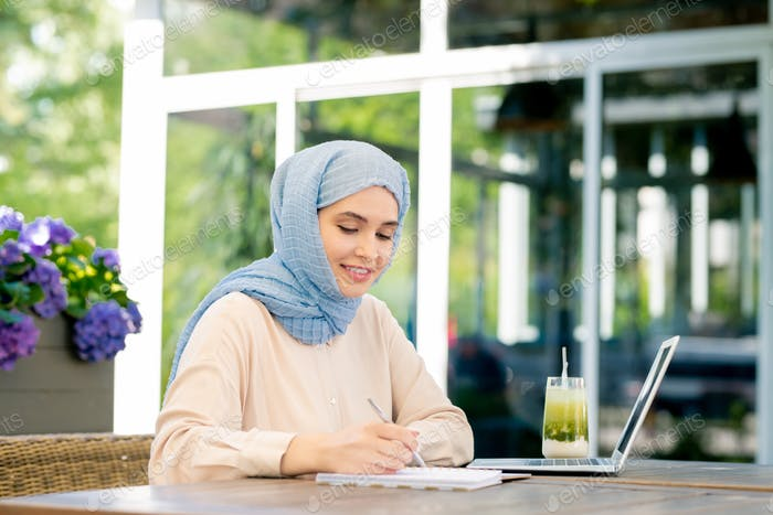 Young muslim student in hijab making working notes by table