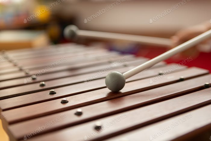 Close-up of mixed-race schoolboy playing xylophone in a classroom at elementary school