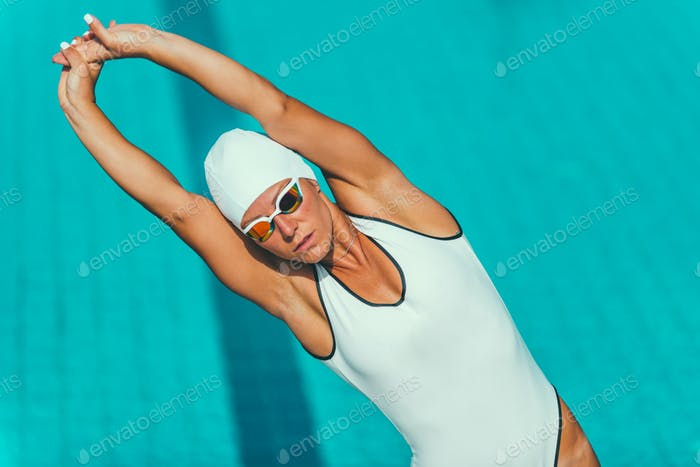 Female swimmer streching on poolside