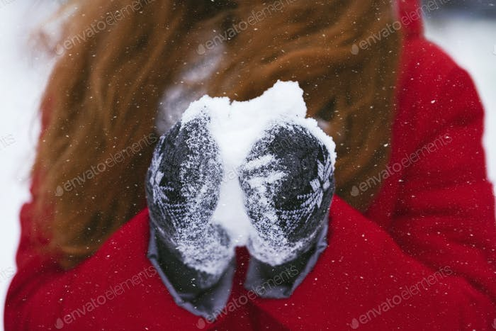 Cropped image of girl holding snowball with warm gloves