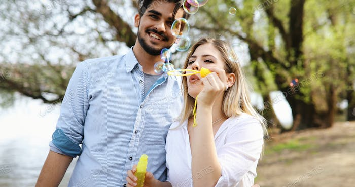 Beautiful young couple blowing soap bubbles and smiling