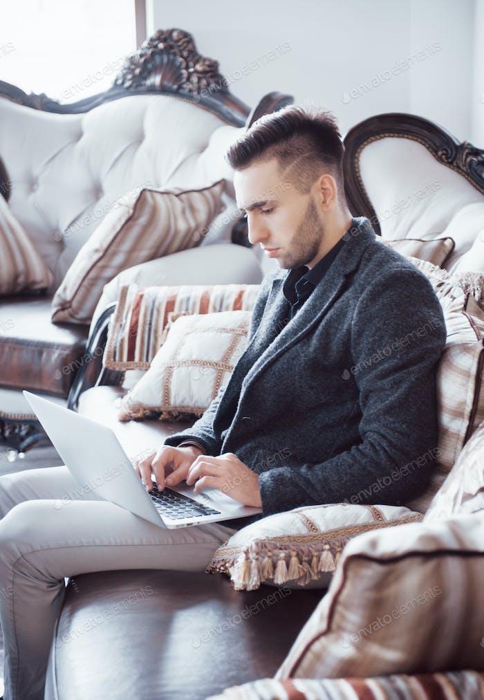 Junger Geschäftsmann, der im Büro arbeitet. Mann trägt weißes Hemd und mit modernen Laptop