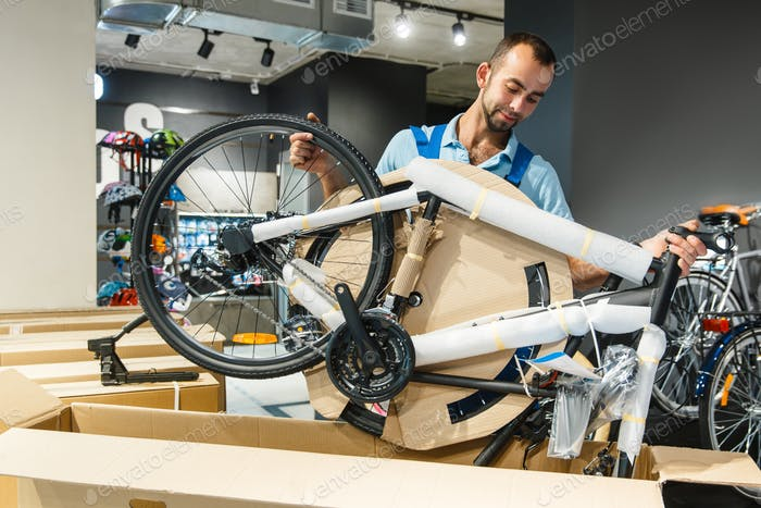 Bicycle workshop, man unpacking box with new bike