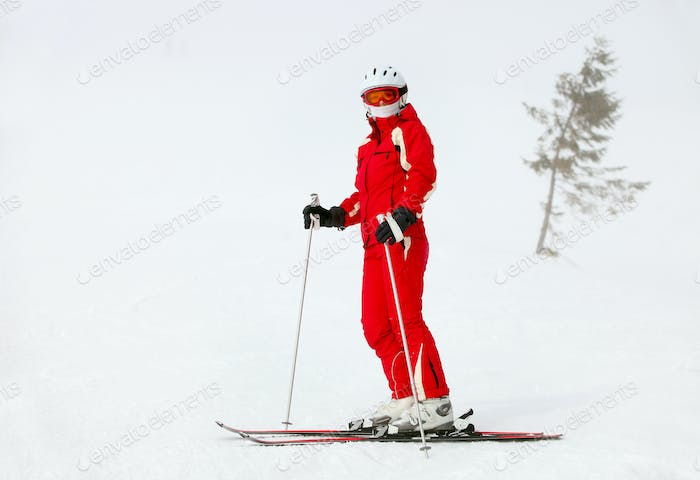 Female skier standing on mountain slope during blizzard