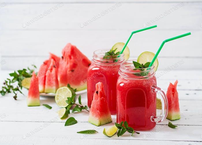 Frische Wassermelonen-Smoothies mit Limette und Minze auf weißem Holzhintergrund
