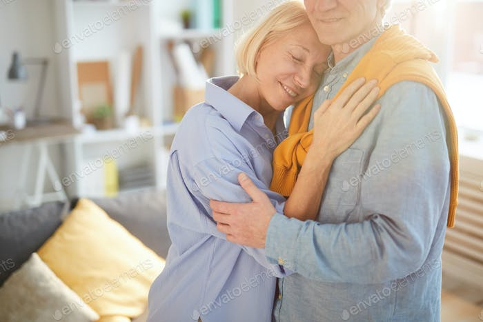 Seniorenpaar umarmen im gemütlichen Zimmer
