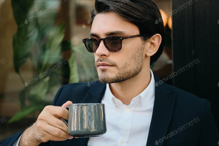 Young handsome man in jacket and sunglasses thoughtfully looking aside holding coffee outdoors
