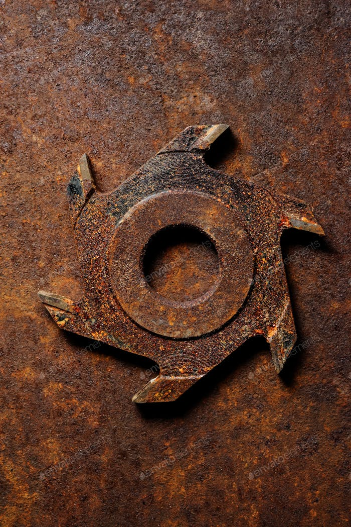 Old milling cutter on rusty metal background