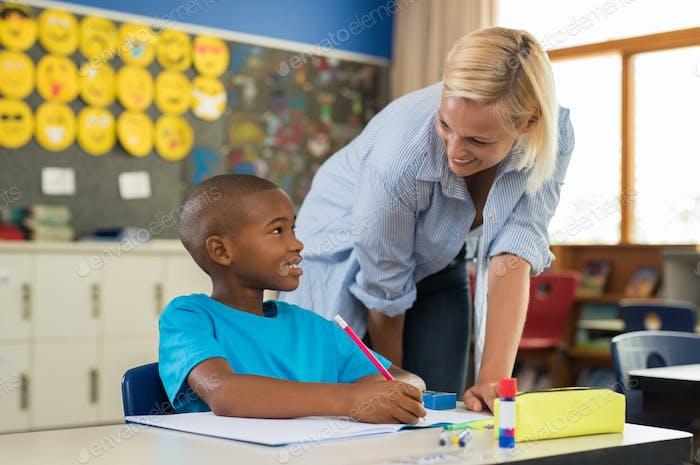 Lehrer helfen Jungen mit Hausaufgaben