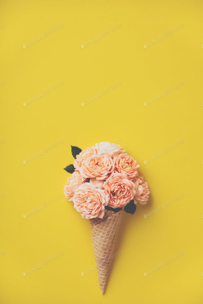 Ice cream cone with pink roses on yellow background