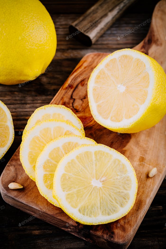 Fresh ripe lemon slices on wooden background