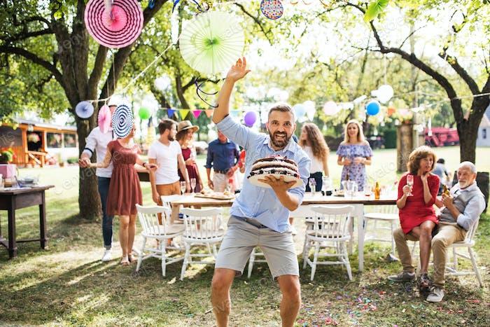 Mann mit einem Kuchen auf einer Familienfeier oder einer Gartenparty draußen.
