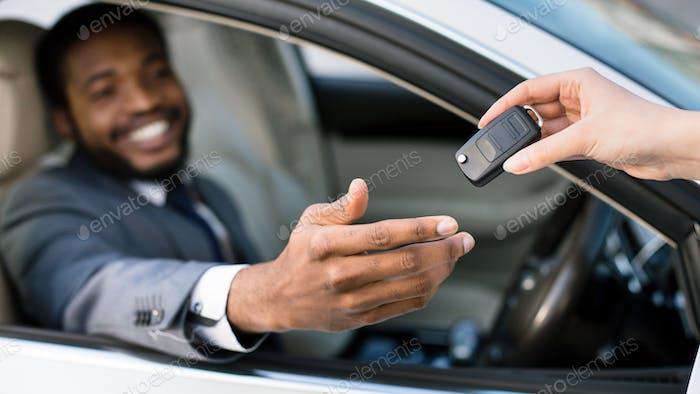 Car salesman giving keys to happy man