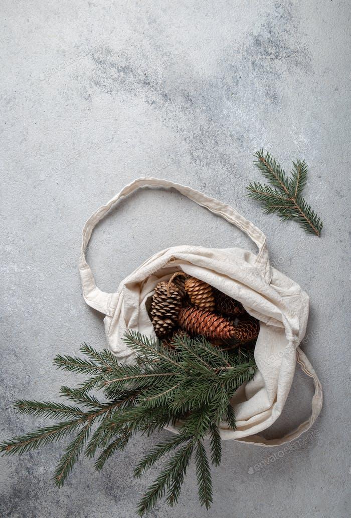 Zero Waste Weihnachtskonzept. Natürliche Chirsmas Dekoration, Tannenzapfen und Zweige im Leinenbeutel.