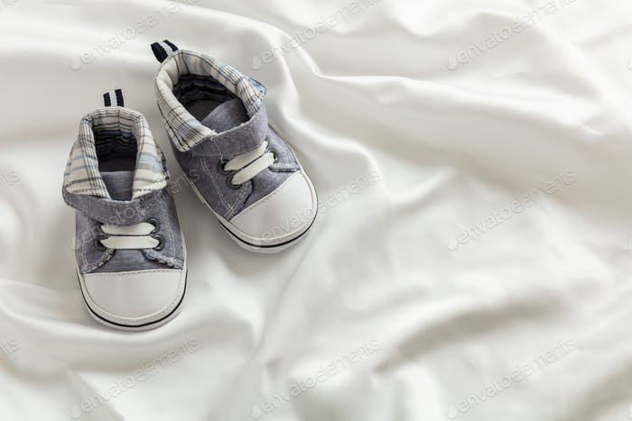 Baby boy shoes  on white satin, copy space