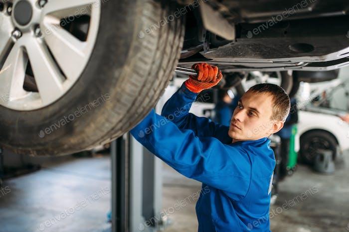 Mechaniker repariert die Federung, Auto auf dem Aufzug