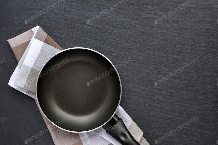 Leere Bratpfanne mit Küchentuch auf dunkelgrauem Stein Backgroun