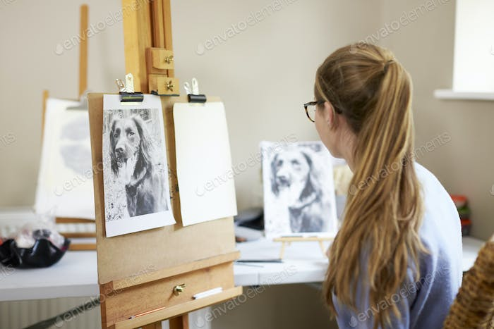 Female Teenage Artist Sitting At Easel Preparing To Draw Picture Of Dog From Photograph