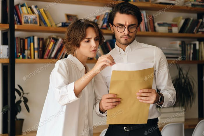 Serious business colleagues standing with envelope letter thoughtfully working together in office