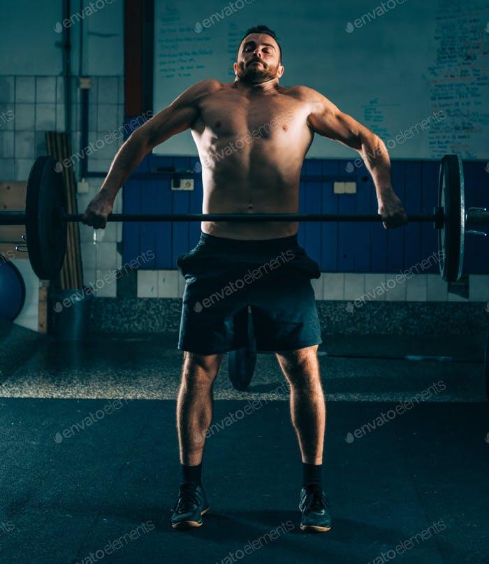 Cross training. Male athlete lifting heavy barbells