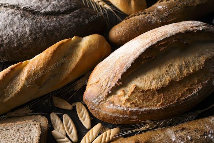 Panadería - panes crujientes rústicos de oro de pan y bollos sobre Fondo de pizarra negro.