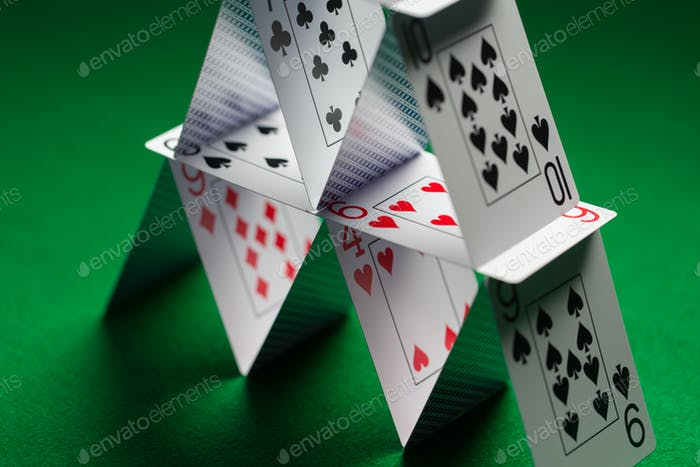 close up of house of playing cards on green cloth