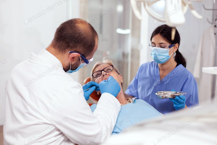 Senior woman getting stomatology treatment