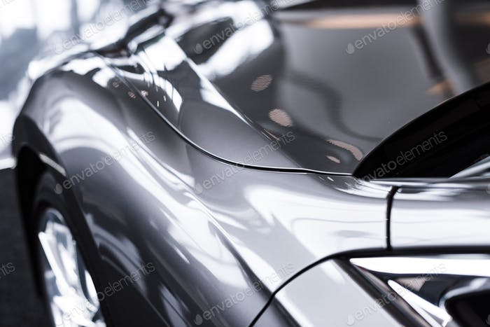 крупным планом вид роскошного блестящего автомобиля в автосалоне