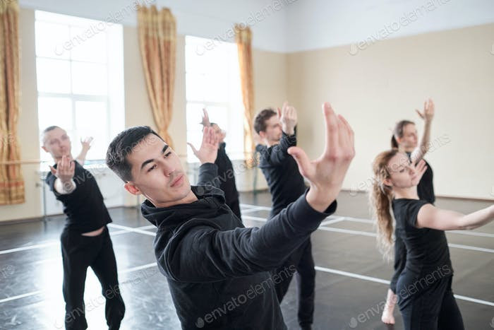 Young handsome man with outstretched arms doing one of dance exercises