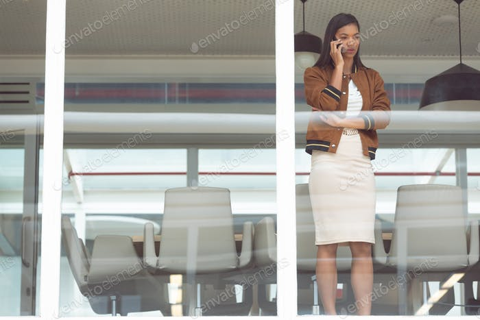 Beautiful mixed race businesswoman talking on mobile phone near window in a modern office