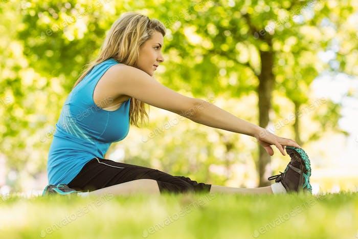 Fit blonde Stretching im Park an einem sonnigen Tag