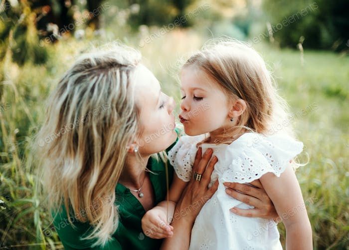 Young mother in nature with small daughter, kissing.