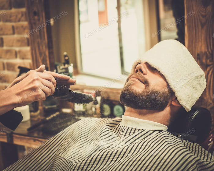 Hairstylist applying  beard powder in barber shop