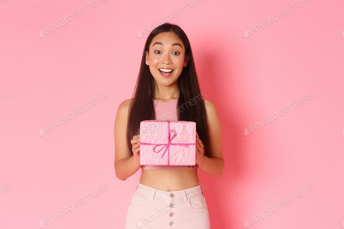 Holidays, celebration and lifestyle concept. Cheerful asian girl celebrating birthday receive